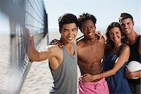 Friends smiling on beach volleyball court Stock Photo - Premium Royalty-Freenull, Code: 635-05972583