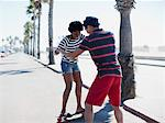 Man teaching girlfriend to skateboard Stock Photo - Premium Royalty-Free, Artist: Blend Images, Code: 635-05972672
