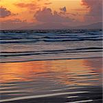 Waves rolling in on beach at sunset Stock Photo - Premium Royalty-Free, Artist: Westend61, Code: 635-05972724