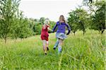 Two Girls Running in Field