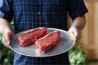 Man holding Tray with Raw Steaks Stock Photo - Premium Royalty-Freenull, Code: 600-05973625