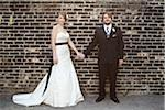 Bride and Groom Standing in front of Brick Wall Stock Photo - Premium Rights-Managed, Artist: Ikonica, Code: 700-05973638