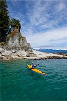 A water level view of a sea kayaker paddling in calm waters along a shoreline near Juneau, Inside Passage, Southeast Alaska, Summer Stock Photo - Premium Rights-Managednull, Code: 854-05974234