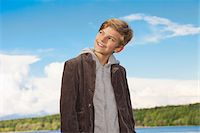 Portrait of a boy looking away and smiling mischievously Stock Photo - Premium Royalty-Freenull, Code: 653-05976317