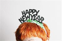 A woman wearing a party tiara with Happy New Year on it, top of head Stock Photo - Premium Royalty-Freenull, Code: 653-05976746