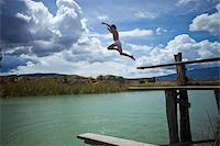 A young boy jumping into a lake Stock Photo - Premium Royalty-Freenull, Code: 653-05976787