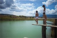 Twin brothers and their friend preparing to jump into a lake Stock Photo - Premium Royalty-Freenull, Code: 653-05976791