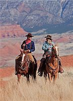 Cowboy and cowgirl riding through Hideout Ranch in Shell, Wyoming, USA Stock Photo - Premium Royalty-Freenull, Code: 682-05976924