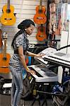 A young woman playing a keyboard in a music shop, Pietermaritzburg, KwaZulu-Natal, South Africa Stock Photo - Premium Royalty-Free, Artist: AWL Images, Code: 682-05977187