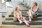Young women putting on rollerskates Stock Photo - Premium Rights-Managed, Artist: Kablonk! RM, Code: 842-05979347