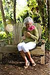 Middle-aged woman relaxing in garden on rustic bench holding flowers Stock Photo - Premium Rights-Managed, Artist: Kablonk! RM, Code: 842-05979402