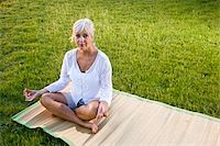 Middle-aged woman sitting on mat practicing yoga outdoors Stock Photo - Premium Rights-Managednull, Code: 842-05979409