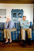 Senior couple sitting on couch, stubborn husband, amused wife Stock Photo - Premium Rights-Managednull, Code: 842-05979533