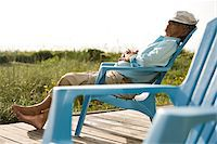 Senior man sitting on chair snoozing in the sun on wood deck Stock Photo - Premium Rights-Managednull, Code: 842-05979544