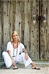 Young blonde woman in white sitting on step in front of wood doors Stock Photo - Premium Rights-Managed, Artist: Kablonk! RM, Code: 842-05979589