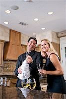 Mid-adult interracial couple opening bottle of champagne in kitchen of home Stock Photo - Premium Rights-Managednull, Code: 842-05979750