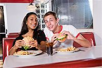 Interracial teen couple eating burgers in restaurant Stock Photo - Premium Rights-Managednull, Code: 842-05979835