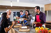 Hispanic mother serving home-cooked meal to family in kitchen Stock Photo - Premium Rights-Managednull, Code: 842-05979919