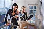 Two young women moving cardboard boxes on hand truck Stock Photo - Premium Rights-Managed, Artist: Kablonk! RM, Code: 842-05979948