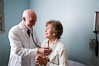 Doctor examining senior woman listening to chest with stethoscope Stock Photo - Premium Rights-Ma