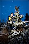 Mid adult man holding tree in cold winter night Stock Photo - Premium Royalty-Freenull, Code: 698-05980205