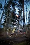 Blurred motion of a man cycling in forest Stock Photo - Premium Royalty-Freenull, Code: 698-05980207