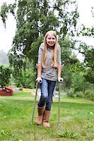 Physically impaired girl with crutches looking away Stock Photo - Premium Royalty-Freenull, Code: 698-05980565