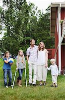 Family with three children standing in back yard Stock Photo - Premium Royalty-Freenull, Code: 698-05980566