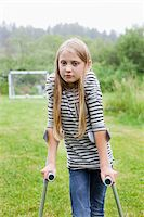 Portrait of girl with crutches in sad mood Stock Photo - Premium Royalty-Freenull, Code: 698-05980573
