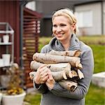 Happy mid adult woman carrying firewood in back yard Stock Photo - Premium Royalty-Free, Artist: Robert Harding Images, Code: 698-05980747