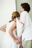 Young siblings holding bouqet of flowers behind backs, peeking through doorway Stock Photo - Premium Royalty-Freenull, Code: 632-05991471