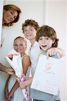Children giving mother flowers and hand-made greeting card Stock Photo - Premium Royalty-Freenull, Code: 632-05991532