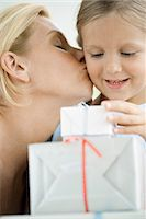 Mother kissing young daughter's cheek as girl looks at wrapped gifts Stock Photo - Premium Royalty-Freenull, Code: 632-05991549