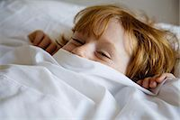 Boy lying in bed with bed sheet covering face Stock Photo - Premium Royalty-Freenull, Code: 632-05991729