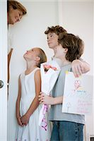 Children giving mother flowers and hand-made greeting card Stock Photo - Premium Royalty-Freenull, Code: 632-05991960