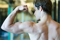Young man flexing bicep muscles Stock Photo - Premium Royalty-Freenull, Code: 632-05992015