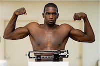 Young man flexing muscle on weight scale, portrait Stock Photo - Premium Royalty-Freenull, Code: 632-05992285