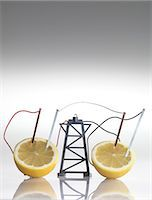 reaction - Electrical circuit with lemons. A chemical reaction between the copper and zinc plates and the lemon produces a small current, that is able to power a light bulb. Stock Photo - Premium Royalty-Freenull, Code: 679-05996491