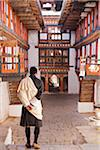 A man at Jakar Dzong wearing a silk shawl known as a kabney over his gho, the national dress for Bhutanese men. Stock Photo - Premium Rights-Managed, Artist: AWL Images, Code: 862-05997009