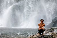 Cambodia, Siem Reap Province, Phnom Kulen. A young man sits shivering by a waterfall after having a swim. Stock Photo - Premium Rights-Managednull, Code: 862-05997271