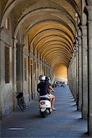 Italy, Tuscany, Lucca. A couple on a motorino under arches in the historic centre Stock Photo - Premium Rights-Managednull, Code: 862-05997959