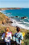 Boy and girl looking down from the cliff-top coast path to Marloes Sands at high tide, Pembrokeshire, Wales. Stock Photo - Premium Rights-Managed, Artist: AWL Images, Code: 862-05999692