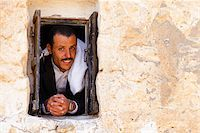 Yemen, Sana'a Province, Haraz Mountains, Al Hajjarah. A man looks out from a window. Stock Photo - Premium Rights-Managednull, Code: 862-05999734