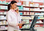 Pharmacist talking on phone at counter Stock Photo - Premium Royalty-Free, Artist: Amy Whitt, Code: 649-06001334