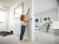 Girl reaching for thermostat Stock Photo - Premium Royalty-Freenull, Code: 649-06001529