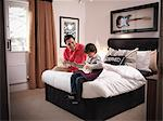 Father and son playing guitar in bedroom Stock Photo - Premium Royalty-Freenull, Code: 649-06001552