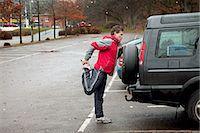 Mature man stretching against car in car park Stock Photo - Premium Royalty-Freenull, Code: 614-06002110