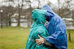 Senior couple in waterproof clothing kissing in park Stock Photo - Premium Royalty-Free, Artist: Janet Foster, Code: 614-06002125