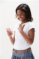 African American girl laughing and holding cellphone, studio shot Stock Photo - Premium Royalty-Freenull, Code: 614-06002408
