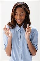 African American teenage girl with fingers crossed, studio shot Stock Photo - Premium Royalty-Freenull, Code: 614-06002423